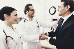Joyful businessman shaking hands with doctor who cured ailment. Acknowledgments. Medical examination. Treatment of disease stock image
