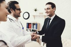 Joyful businessman shaking hands with doctor who cured ailment. Acknowledgments. royalty free stock photography