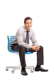 Joyful businessman sitting on a blue chair Royalty Free Stock Photography
