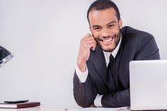 Joyful businessman. Smiling African businessman sitting at the t Royalty Free Stock Photos