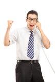 Joyful businessman talking on telephone. Vertical shot of a joyful businessman talking on telephone isolated on white background Stock Photo
