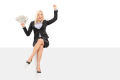 Joyful businesswoman holding money seated on panel Royalty Free Stock Image