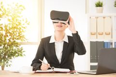 Joyful businesswoman holding VR goggles. Joyful businesswoman sitting on a working desk at bright sunlight office and holding VR goggles watching 3D video Stock Photo