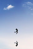 Joyful businesswoman leaps on the clear sky. Silhouette of successful businesswoman jumping and celebrating her success on the sky with reflection of her shadow Royalty Free Stock Photos