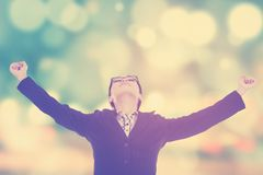 Joyful businesswoman raised hands. Portrait of successful female worker celebrating her victory and raised hands, shot with a blur background Royalty Free Stock Photography