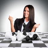 Joyful businesswoman wins chess and raised his. Hands up. Business concept Stock Photo