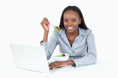 Joyful businesswoman working. With a laptop while eating a salad against a white background Royalty Free Stock Photography