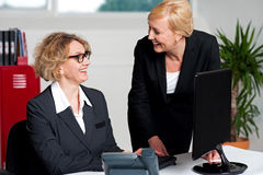 Joyful businesswomen enjoying at work desk Stock Photos