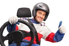 Joyful car racer giving a thumb up Stock Photos