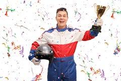 Joyful car racer holding a gold trophy Royalty Free Stock Photos
