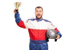 Joyful car racer holding a golden trophy Royalty Free Stock Image