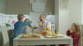 Family at home eating breakfast in kitchen together stock footage