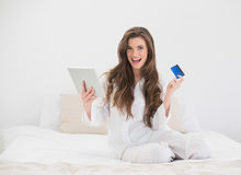 Joyful casual brown haired woman in white pajamas shopping online with her tablet pc Stock Photo