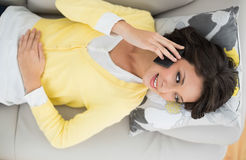 Joyful casual brunette in yellow cardigan making a phone call Stock Photo