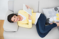 Joyful casual brunette in yellow cardigan using a tablet pc Royalty Free Stock Photos