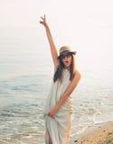 Joyful casual girl walking on a sea beach and happy screaming. Stock Photos