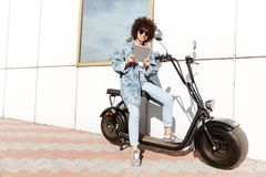 Joyful casual woman in sunglasses using tablet computer. While sitting on a motorbike outdoors Royalty Free Stock Images