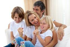 Joyful caucasian familj som sitter i vardagsrumet arkivfoto