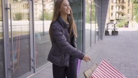 Joyful caucasian girl walking on the street with shopping bags. Happy woman satisfied with her purchases. Shopaholism. Joyful caucasian girl walking on the stock footage