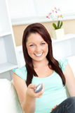 Joyful caucasian woman holding a remote smiling Royalty Free Stock Photo