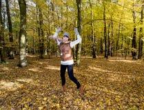 Joyful caucasian woman jumping in the autumn leaves Royalty Free Stock Photos