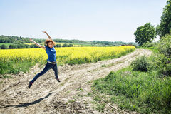 Joyful caucasian woman is jumping in rapeseed field Stock Images