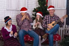 Joyful celebration in the family. Parents and teens children, in a Santa hats, are having fun and expressive singing in front of a Christmas tree, in Stock Image