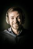 Joyful charismatic man listening to music Stock Images