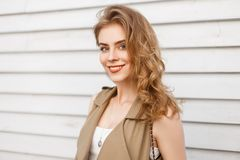 Joyful charming young woman with natural make-up with curly blond hair in a stylish vest is smiling. And looking into the camera near a white vintage wooden stock photo