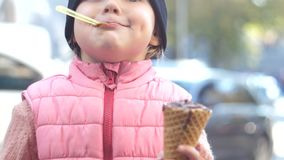 Joyful and cheerful baby girl eating chocolate ice cream with a waffle cone, delicious dessert 4k. stock video footage