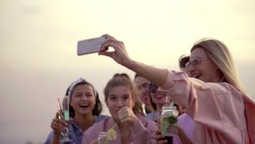 Joyful and cheerful company of friends drink cocktails and take selfies on the phone. summer urban cocktail stock video footage