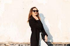 Joyful cheerful hipster young woman in trendy sunglasses in stylish coat in white jeans with a black handbag posing. Near a white wall on a bright sunny day stock photos