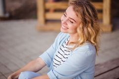 Fashion portrait of happy stunning curly blonde girl with beautiful smile in the city street. stock photography