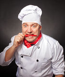 Joyful chef. A joyful chef with chilly pepper in his mouth Royalty Free Stock Photos