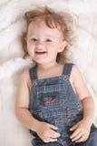 Joyful child. Joyful laughing child lying on the white fur carpet Stock Photo