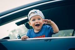 Joyful child in the car waving his hand Royalty Free Stock Photos