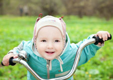 Joyful child at the children's bike Royalty Free Stock Images