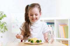 Joyful child eating healthy food at home Royalty Free Stock Photos