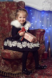 Joyful child with a gift near the Christmas tree royalty free stock photos