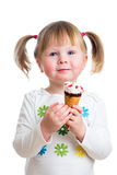 Joyful child girl eating ice cream in studio isolated Stock Image