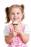 Joyful child girl eats ice cream in studio isolated Royalty Free Stock Images