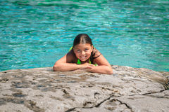 Joyful child girl lying and relaxing on the edge of the cliff against gorgeous amazing Cyprus lake background Royalty Free Stock Photo