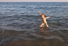 Joyful child jumps out of the sea. Royalty Free Stock Images