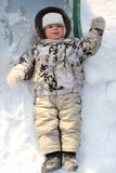 The joyful child lays on a snow Royalty Free Stock Photography