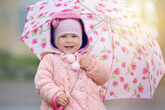 Joyful child with pink flower umbrella in the sun light after rain