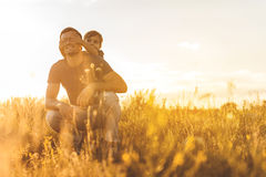 Joyful child playing with his dad on grassland Stock Image
