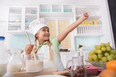Joyful child preparing dough in kitchen Stock Image