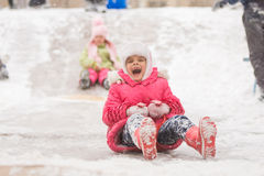 Joyful child rolls a seven-year ice slides. Seven year old girl riding a ledyankah winter on a snowy hill surrounded by other children Stock Photo