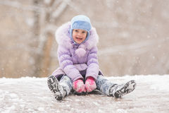 Joyful child slides down the icy hill. Five-year girl riding winter on a snowy hill surrounded by other children Stock Photo