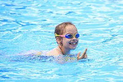 Joyful child in swimming glasses in the pool. Joyful child in swimming glasses in the outdoor pool Royalty Free Stock Photography